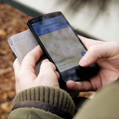 A man holding a smartphone looking at a Google maps